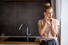 Młoda blond dziewczyna używa jej mądrze telefon w kuchni zdjęcie stock