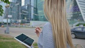 Młoda blond dziewczyna używa pastylkę na tle drapacze chmur w centrum zbiory wideo