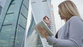 Młoda blond dziewczyna używa pastylkę na tle drapacze chmur w centrum zdjęcie wideo