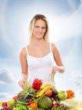 Młoda blond kobieta i stos świeże owoc Zdjęcie Stock