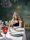 Młoda blond kobieta jest ubranym koronę w czarodziejskim luksusowym wnętrzu z pustymi antykwarskimi ramami sumuje bogactwo Obraz Royalty Free