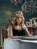 Młoda blond kobieta jest ubranym koronę w czarodziejskim luksusowym wnętrzu z pustymi antykwarskimi ramami sumuje bogactwo Fotografia Stock