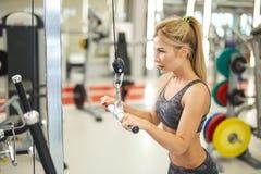 Młoda blond kobieta robi ćwiczeniu dla ona w nowożytnym gym z powrotem obrazy stock