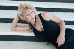 Młoda blond kobieta w czerni na białym i czarnym tle Zdjęcia Stock