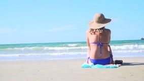 Młoda blond kobieta z błękitnym bikini i słomianym kapeluszem siedzi na spojrzeniach przy morzem i plaży zbiory wideo