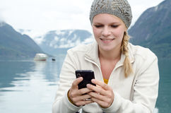 Młoda blond kobieta z jej Smartphone w ręce Obraz Stock