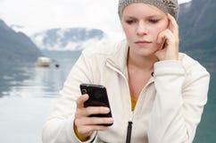 Młoda blond kobieta z jej Smartphone w ręce zdjęcie royalty free