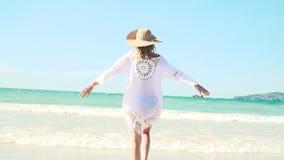 Młoda blond kobieta z kapeluszem i białą tuniką rusza się na tajlandzkiej plaży zbiory
