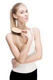 Młoda blond kobiety mienia grępla szczotkuje na bielu Obrazy Stock
