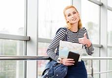 Młoda blond kobiety pozycja i przedstawienie kciuk w kamerę, mienie i plecaka, karciana pastylka Zdjęcie Royalty Free