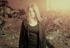 Młoda blond z włosami dziewczyna pozuje samotnie w slamsach backlit, stonowany colorized wizerunek obrazy stock