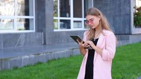 Młoda blondynka pracuje na pastylka komputerze osobistym w mieście Żeński używa bezprzewodowy internet na ulicie Komunikaci mobil zbiory wideo