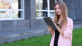 Młoda blondynka pracuje na pastylka komputerze osobistym w mieście Żeński używa bezprzewodowy internet na ulicie Komunikaci mobil zdjęcie wideo