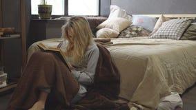 Młoda blondynka siedzi na podłoga w koc obok łóżka i czyta książkę zbiory