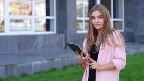 Młoda blondynka stoi z pastylką w ona ręki Żeński używa bezprzewodowy internet na ulicie banner komunikacja jest globus telefonów zbiory