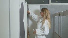Młoda blondynka w bathrobe używa smartphone w przebieralni zbiory