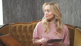 Młoda blondynka w różowym kostiumu używa zakładka komputer i ono uśmiecha się zbiory wideo