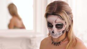 Młoda blondynka z bukietem czerń kwiaty i makeup w postaci kośca zdjęcie wideo
