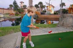Młoda blondynki chłopiec bawić się miniaturowego golfa obrazy royalty free