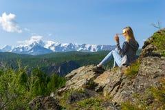 Młoda blondynki dziewczyna na skale na pogodnym ciepłym jesień letnim dniu ponownym fotografia stock