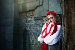 Młoda blondynki dziewczyna płacze krwiste łzy w cmentarzu Obrazy Stock