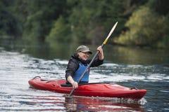 Młoda blondynki dziewczyna pływa na sporta łódkowatym kajaku na pięknym ri zdjęcie royalty free