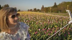 Młoda blondynki dziewczyna robi selfie przy tulipanu polem zdjęcie wideo