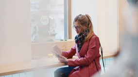 Młoda blondynki dziewczyna używa jej przyrząd w café, dotykający jej szkła, ślizga się ekran sensorowego Elegancki strój, wygodn zdjęcie wideo