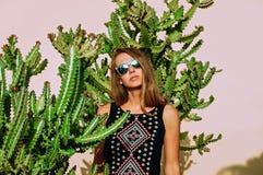 Młoda blondynki dziewczyna w kolorowych okularach przeciwsłonecznych pozuje w tropikalnych roślinach Atrakcyjna kobieta na kaktus Obraz Royalty Free