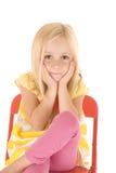 Młoda blondynki dziewczyna w kolorze żółtym paskował koszulowego obsiadanie w czerwonym krześle c Zdjęcie Royalty Free
