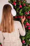 Młoda blondynki dziewczyna z uszatą grzałką na głowie stawia Bożenarodzeniową czerwoną dekorację na drzewie Zdjęcie Stock
