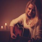 Młoda blondynki kobieta bawić się gitarę w świeczki świetle Fotografia Stock
