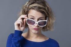 Młoda blondynki kobieta bawić się z jej dużymi okularami przeciwsłonecznymi Obrazy Stock