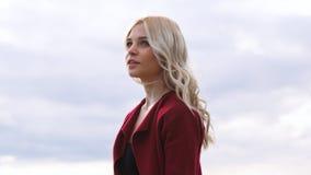 Młoda blondynki kobieta mieć_nadzieja w czerwieni przeciw chmurnemu niebu - marzący, czekający, Emocjonalny ?e?ski portret kosmos zdjęcie stock