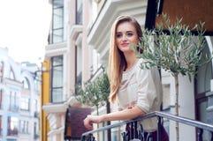 Młoda blondynki kobieta na jej balkonu ono uśmiecha się obraz royalty free