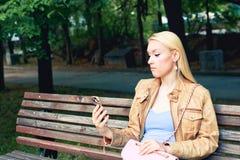 Młoda blondynki kobieta patrzeje jej smartphone i myśleć czego colling Negatywna reakcja wezwanie zdjęcia royalty free