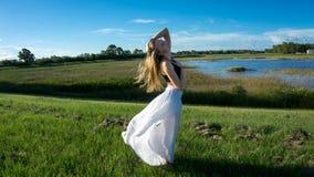 młoda blondynki kobieta pozuje przeciw wiatrowi w krajobrazie z pokojową twarzą podczas zmierzch spódnicy dmuchających wiatrem wł zdjęcia stock