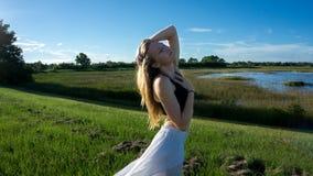 młoda blondynki kobieta pozuje przeciw wiatrowi w krajobrazie z pokojową twarzą podczas zmierzch spódnicy dmuchających wiatrem wł obraz royalty free