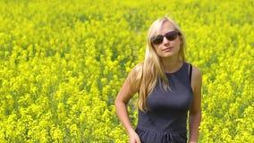 Młoda blondynki kobieta pozuje w pięknym rapeseed polu zbiory