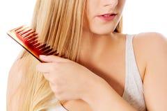 Młoda blondynki kobieta szczotkuje jej włosy Fotografia Royalty Free