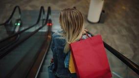 Młoda blondynki kobieta w cajg kurtce iść puszek na poruszających schodach w zakupy centrum handlowym zbiory