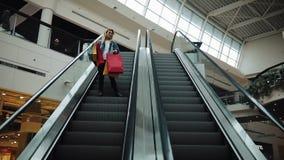 Młoda blondynki kobieta w cajg kurtce iść puszek na poruszających schodach w zakupy centrum handlowym zdjęcie wideo