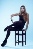 Młoda blondynki kobieta w czarnym swimsuit obsiadaniu na krzesła pozować obraz stock