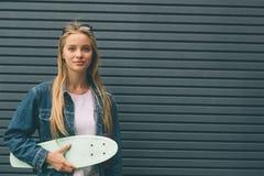 Młoda blondynki kobieta z deskorolka w jego ręce przeciw tłu Pasiasta ściana Zdjęcie Stock