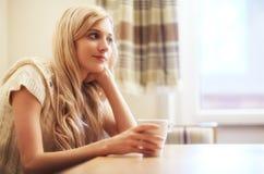 Młoda blondynki kobieta z filiżanką przy stołem Fotografia Stock
