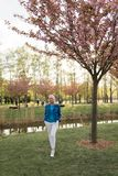 Młoda blondynki matki kobieta cieszy się czas wolnego - Ubierającego w niebieskiej marynarki i bielu spodniach zdjęcie stock