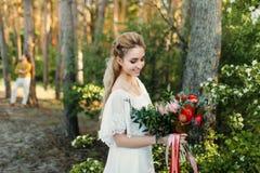 Młoda blondynki panna młoda z nieociosanym bukietem jest pozować plenerowy w parku grafika Jesieni ślubna ceremonia outdoors zdjęcia royalty free