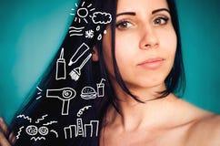 Młoda brunetka pokazuje różnych niszczy czynników dla włosy obraz stock