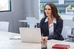Młoda brunetka pracuje przy jej biurkiem przy jej biurem obrazy stock