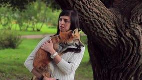 Młoda brunetka trzyma pomarańczowego lisa i muska ona w parku w lecie zbiory